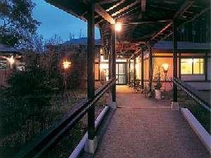 白水温泉 竹の倉山荘:【外観】かがり火が焚かれ、本館玄関へとつづく夜の幻想的なアプローチ。