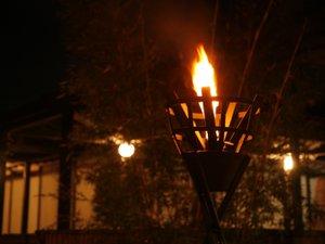 【夜景】かがり火が焚かれる幻想的な玄関は別世界のよう。