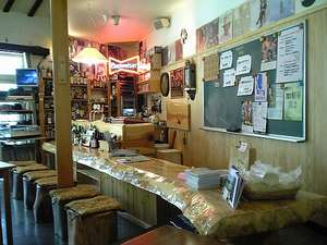 湖畔の小さなリゾート サウンズグッド!:バーカウンターは4.5mのトチノキ。バックバーの黒板でイベントやオススメのお酒、おつまみをチェック!