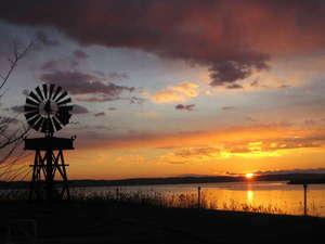 北浦宝来温泉つるるんの湯宿 北浦湖畔荘:朝焼けに染まる湖面と風車