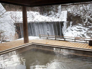 かやぶきの郷薬師温泉 旅籠:滝見乃湯:目の前を流れる温川(ぬるかわ)の滝を見ながら雪景色をお楽しみいただけます。