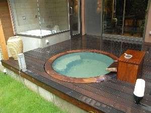 タイムリゾート隠れ屋:風呂例・かりんの木を使った露天風呂。お湯がエメラルドグリーンに見える