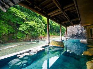 渓谷に佇む源泉湯宿 四万やまぐち館:【お題目大露天風呂】四万川に面した、浴槽は長さ30mで開放感抜群。お題目を刻んだ大岩が目を引きます。