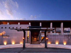 夕暮れ時に柔らかい光が灯る、美術館のような外観のホテルです。