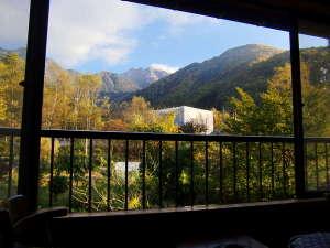 旅館 観岳:夕日に照らされる活火山『焼岳』色づいた木々は夕日のスポットライトに照らされ益々色を豊かにします。