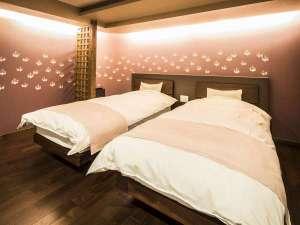 京の片泊まり 稚松こうばい庵:1階ベッド。シーリーのマットレスとこだわりの寝具をご用意。紅梅色の唐紙の壁紙が特徴です。