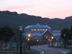 うらかわ優駿ビレッジAERU(アエル):淡いピンクの夕焼け。アエル手前のアプローチに灯がともり、もうすぐ夕食の時間です。