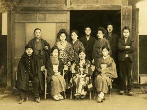 【創業当時の初代ヤスと一族】右上の看板に松月の「松」の字が見える。昭和初期。