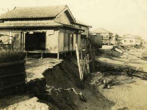 【侵蝕される海岸と松月】軒下まで波に洗われている。建物自体の流出の危機が続いた。昭和初期。