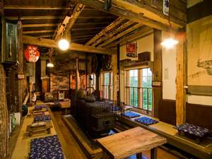 オーベルジュ北の暖暖:開拓時のとん田造りの館内。大きな薪ストーブがあるロビー