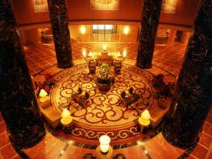 ホテルオークラ福岡:ダーク・ワインレッドの大理石の柱と、壁面を飾る鮮やかな絵画が、壮麗なミュージアムを彷彿させるロビー。