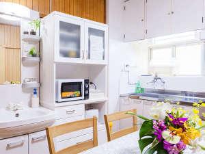 かりゆしコンドミニアムリゾート那覇 you家(ゆうや):キッチン&リビングルーム。2ドア冷蔵庫・電子レンジなどの調理器具と食器を完備しております。