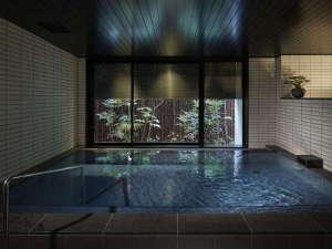【大浴場・御池の湯】天然鉱石「トゴール・ウォームタイト」を使用し、温泉成分を再現しています。