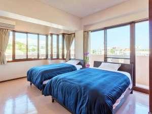 かりゆしコンドミニアムリゾート沖縄 MEZON MAX(メゾンマックス):<3階>ぐるりと囲んだ明るい窓が特徴。主賓室にはセミダブルベッドが2台。バスルーム2つ。
