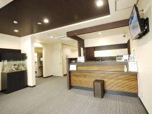 ビジネスホテルフィズ名古屋空港(旧サンクロック名古屋空港):正面玄関からフロント 横には熱帯魚水槽があり、ホワイトとブラウンを基調としたおちついた雰囲気を。