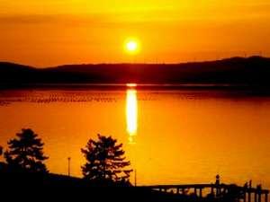 十番館:この写真、屋上からワタシが撮りました。ホントですよ。夕日の七尾湾。桟橋には釣り人が3人。