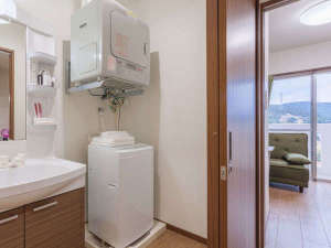 かりゆしコンドミニアムリゾート金武 ヤカシーサイド:【室内】洗面所からリビング、寝室を望む。室内洗濯機(4.2kg)とガス乾燥機を完備。便利にご利用下さい。