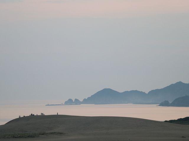 日の出を見ようと馬の背に登っている人々。_鳥取砂丘オアシス広場