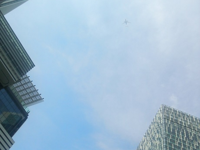 ビル群遥か上空を飛ぶ飛行機_JR名古屋駅