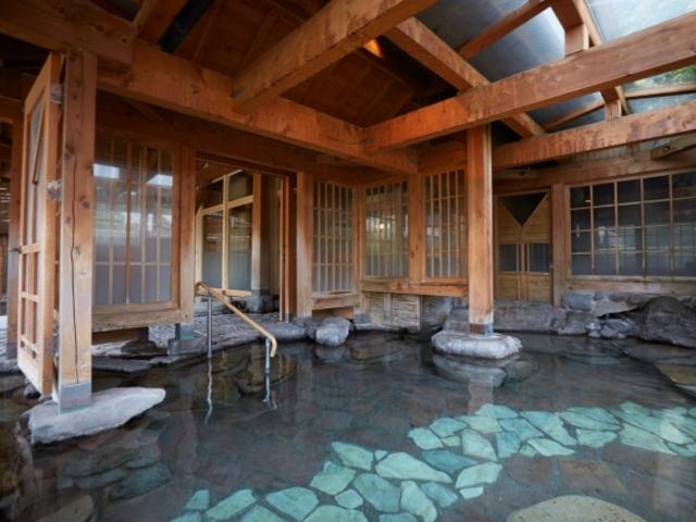 半露天岩風呂:雨が降った際にも外の景色を楽しんで頂けるガラス窓に囲まれた空間です。_名苑と名水の宿 梅園