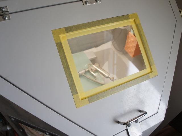 両手をブラスター(機械)の中に入れて小窓から見ながら砂を吹き付けます。_砂吹工房ハシゴヤ